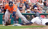 Rajai Davis of the Detroit Tigers steals third base as third baseman Luis Valbuena of the Houston Astros drops the ball during the sixth inning at...