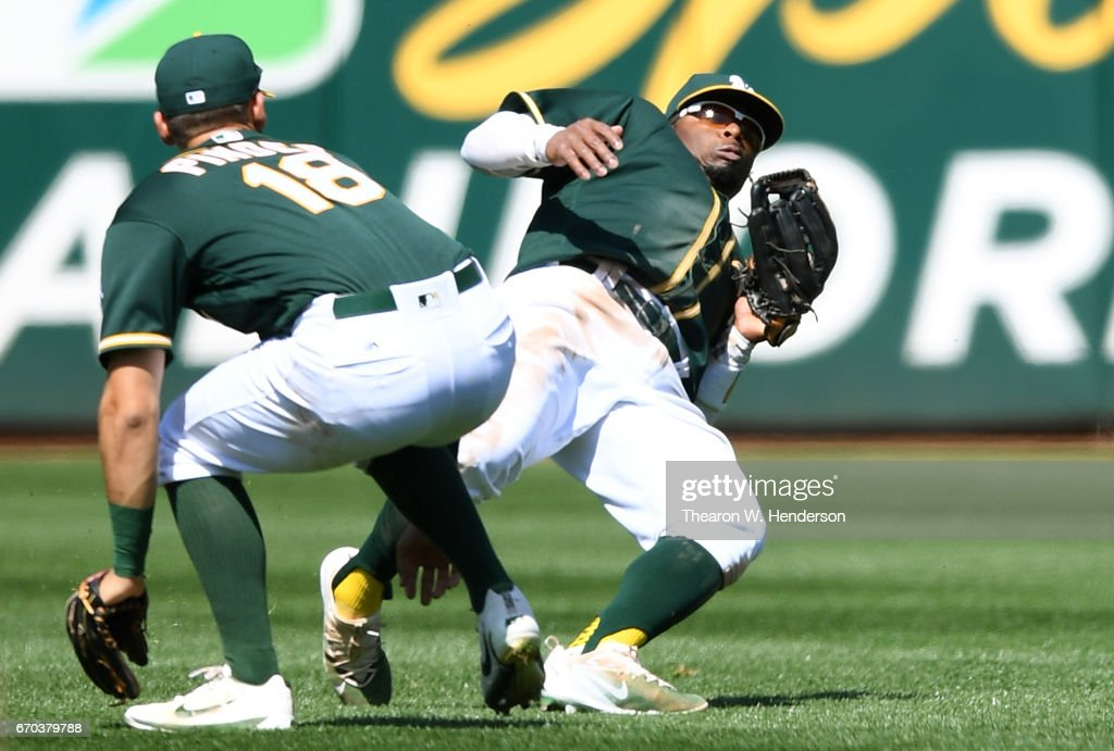 Rajai Davis #11 of the Oakland Athletics avoids colliding with Chad Pinder #18 while catching a fly ball off the bat of Jurickson Profar of the Texas Rangers in the top of the seventh inning at Oakland Alameda Coliseum on April 19, 2017 in Oakland, California. The Athletics won the game 9-1.