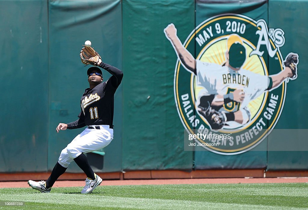Rajai Davis #11 of the Oakland Athletics catches a ball hit by Pablo Sanodoval of the San Francisco Giants in the first inning during an MLB game at the Oakland-Alameda County Coliseum on May 22, 2010 in Oakland, California.