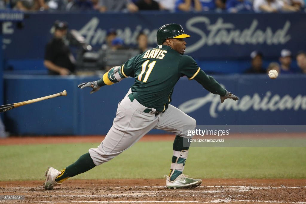 Rajai Davis #11 of the Oakland Athletics hits a soft groundout as he breaks out of the batter's box before being thrown out by Miguel Montero #47 of the Toronto Blue Jays in the seventh inning during MLB game action at Rogers Centre on July 26, 2017 in Toronto, Canada.
