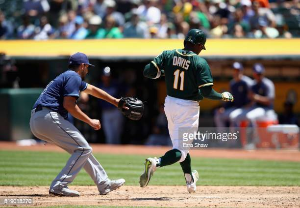 Rajai Davis of the Oakland Athletics scores on a wild pitch by Jacob Faria of the Tampa Bay Rays in the fifth inning at Oakland Alameda Coliseum on...