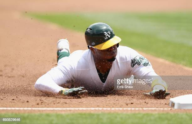 Rajai Davis of the Oakland Athletics steals third base in the first inning against the Toronto Blue Jays at Oakland Alameda Coliseum on June 7 2017...