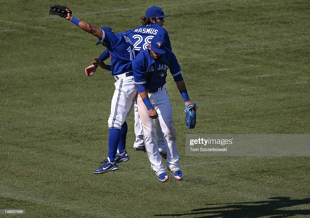 <a gi-track='captionPersonalityLinkClicked' href=/galleries/search?phrase=Rajai+Davis&family=editorial&specificpeople=810608 ng-click='$event.stopPropagation()'>Rajai Davis</a> #11 of the Toronto Blue Jays celebrates their victory with Jose Bautista #19 and <a gi-track='captionPersonalityLinkClicked' href=/galleries/search?phrase=Colby+Rasmus&family=editorial&specificpeople=3988372 ng-click='$event.stopPropagation()'>Colby Rasmus</a> #28 during MLB game action against the Cleveland Indians on July 14, 2012 at Rogers Centre in Toronto, Ontario, Canada.