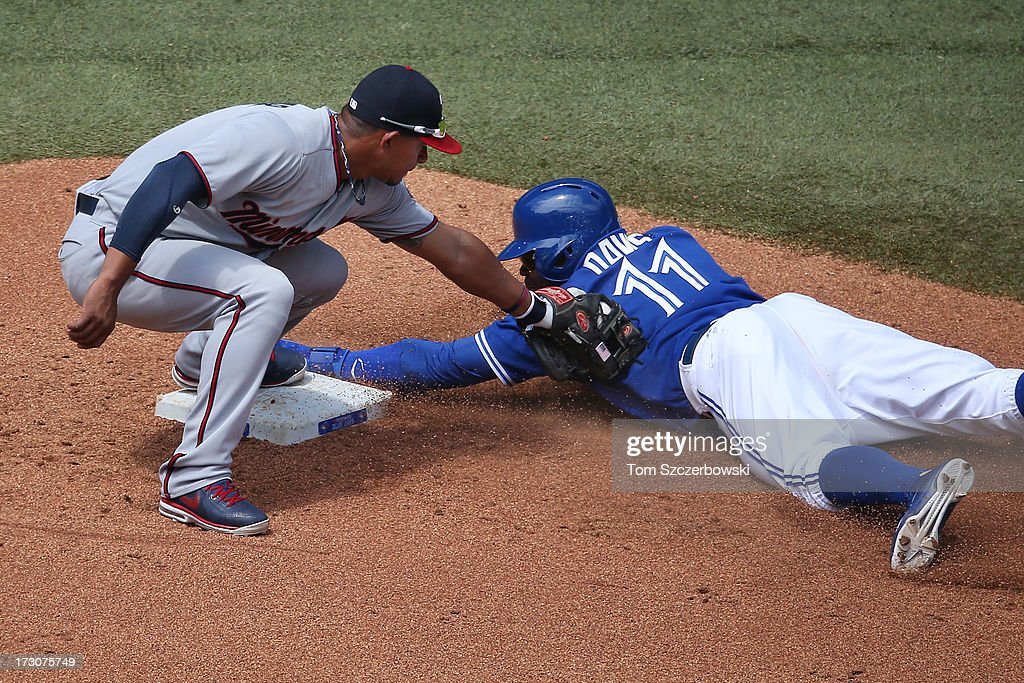 <a gi-track='captionPersonalityLinkClicked' href=/galleries/search?phrase=Rajai+Davis&family=editorial&specificpeople=810608 ng-click='$event.stopPropagation()'>Rajai Davis</a> #11 of the Toronto Blue Jays is caught stealing in the fourth inning during MLB game action as <a gi-track='captionPersonalityLinkClicked' href=/galleries/search?phrase=Eduardo+Escobar&family=editorial&specificpeople=7522733 ng-click='$event.stopPropagation()'>Eduardo Escobar</a> #5 of the Minnesota Twins tags him out on July 6, 2013 at Rogers Centre in Toronto, Ontario, Canada.