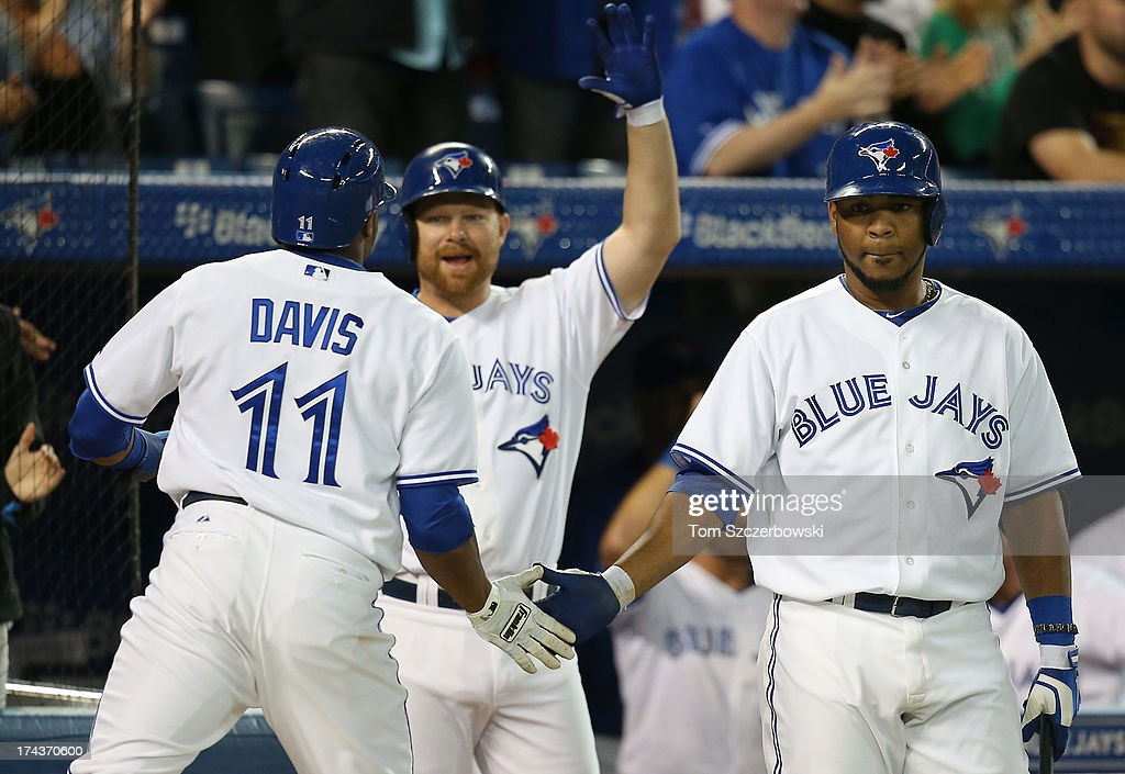 <a gi-track='captionPersonalityLinkClicked' href=/galleries/search?phrase=Rajai+Davis&family=editorial&specificpeople=810608 ng-click='$event.stopPropagation()'>Rajai Davis</a> #11 of the Toronto Blue Jays is congratulated by <a gi-track='captionPersonalityLinkClicked' href=/galleries/search?phrase=Edwin+Encarnacion&family=editorial&specificpeople=598285 ng-click='$event.stopPropagation()'>Edwin Encarnacion</a> #10 and <a gi-track='captionPersonalityLinkClicked' href=/galleries/search?phrase=Adam+Lind&family=editorial&specificpeople=3911783 ng-click='$event.stopPropagation()'>Adam Lind</a> #26 after scoring a run in the eighth inning during MLB game action against the Los Angeles Dodgers on July 24, 2013 at Rogers Centre in Toronto, Ontario, Canada.