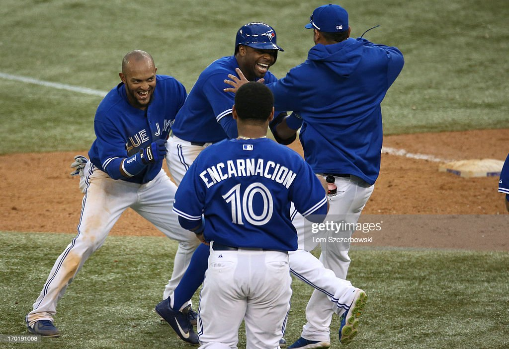 <a gi-track='captionPersonalityLinkClicked' href=/galleries/search?phrase=Rajai+Davis&family=editorial&specificpeople=810608 ng-click='$event.stopPropagation()'>Rajai Davis</a> #11 of the Toronto Blue Jays is congratulated by <a gi-track='captionPersonalityLinkClicked' href=/galleries/search?phrase=Emilio+Bonifacio&family=editorial&specificpeople=4193706 ng-click='$event.stopPropagation()'>Emilio Bonifacio</a> #1 and Esmil Rogers #32 after driving in the winning run in the eighteenth inning during MLB game action against the Texas Rangers on June 8, 2013 at Rogers Centre in Toronto, Ontario, Canada.