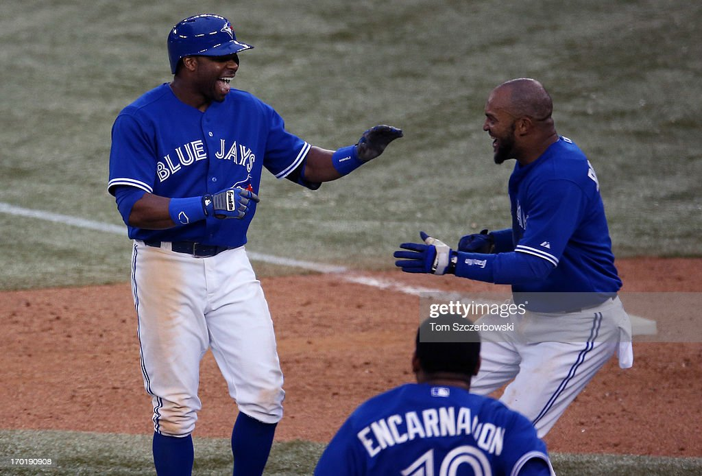 <a gi-track='captionPersonalityLinkClicked' href=/galleries/search?phrase=Rajai+Davis&family=editorial&specificpeople=810608 ng-click='$event.stopPropagation()'>Rajai Davis</a> #11 of the Toronto Blue Jays is congratulated by <a gi-track='captionPersonalityLinkClicked' href=/galleries/search?phrase=Emilio+Bonifacio&family=editorial&specificpeople=4193706 ng-click='$event.stopPropagation()'>Emilio Bonifacio</a> #1 after driving in the winning run in the eighteenth inning during MLB game action against the Texas Rangers on June 8, 2013 at Rogers Centre in Toronto, Ontario, Canada.