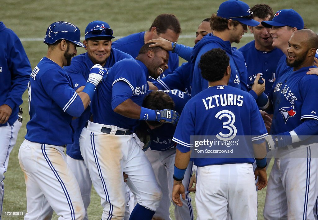 <a gi-track='captionPersonalityLinkClicked' href=/galleries/search?phrase=Rajai+Davis&family=editorial&specificpeople=810608 ng-click='$event.stopPropagation()'>Rajai Davis</a> #11 of the Toronto Blue Jays is mobbed by teammates after driving in the winning run in the eighteenth inning during MLB game action against the Texas Rangers on June 8, 2013 at Rogers Centre in Toronto, Ontario, Canada.