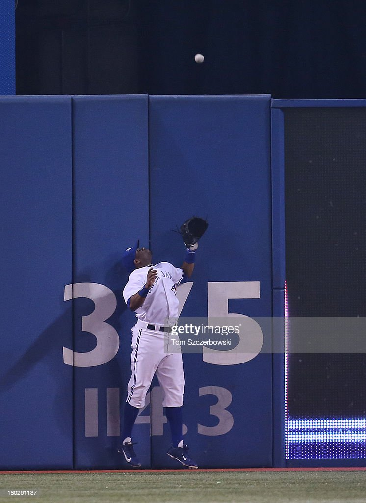 <a gi-track='captionPersonalityLinkClicked' href=/galleries/search?phrase=Rajai+Davis&family=editorial&specificpeople=810608 ng-click='$event.stopPropagation()'>Rajai Davis</a> #11 of the Toronto Blue Jays watches a solo home run go over the wall during MLB game action in the fifth inning off the bat of <a gi-track='captionPersonalityLinkClicked' href=/galleries/search?phrase=Mark+Trumbo&family=editorial&specificpeople=4921667 ng-click='$event.stopPropagation()'>Mark Trumbo</a> (not pictured) of the Los Angeles Angels of Anaheim on September 10, 2013 at Rogers Centre in Toronto, Ontario, Canada.
