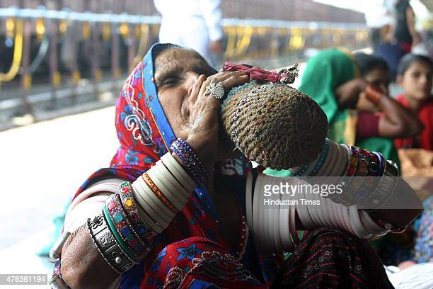 Rajasthani woman uses a traditional cool water pitcher to quench her thirst at the Bhopal railway station even as the day remained extremely hot and...