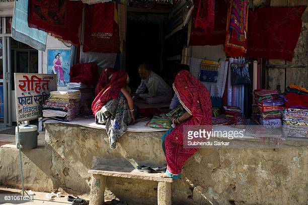 SEKHAWATI NAWALGARH RAJASTHAN INDIA Rajasthani women in traditional dress buy saris at a shop