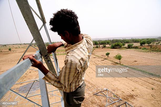 Rajeev working on under construction High Tension electric tower on June 9 2012 in Sohna India The prospect of more income lures men to work at...