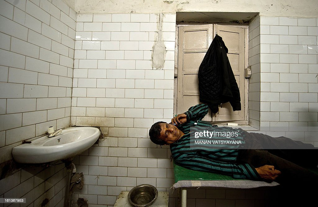 Rajesh, 45, talks on his mobile phone as he lies on a bed at the Railway Hospital in Allahabad on February 10, 2013 after being injured in a stampede that killed at least 10 people at the main railway station serving India's giant Kumbh Mela festival. Dozens more were injured in the crush and some local television channels put the death toll as high as 20. Local officials said that the railings on a bridge at Allahabad station had given way under the pressure of the mass of people, while eyewitnesses told local media that the police had baton-charged the crowd leading to panic. AFP PHOTO/ MANAN VATSYAYANA