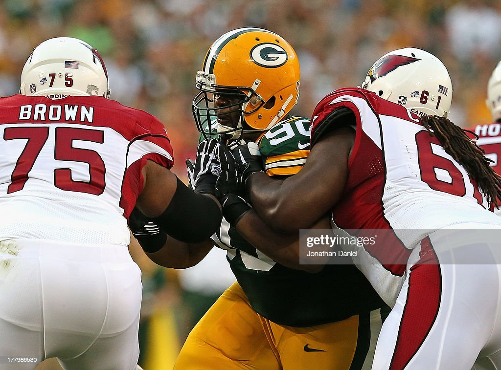 B.J. Raji #90 of the Green Bay Packers rushes against Levi Brown #75 and Jonathan Cooper #61 of the Arizona Cardinals at Lambeau Field on August 9, 2013 in Green Bay, Wisconsin. The Cardinals defeated the Packers 17-0.