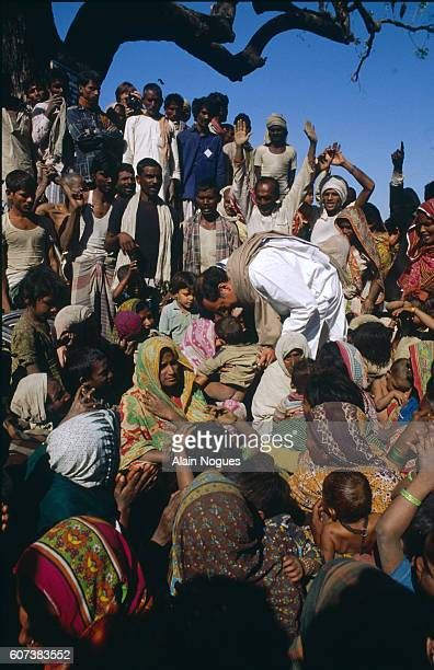 Rajiv Gandhi is surrounded by women and children during a visit to Uttar Pradesh for his legislative election campaign leading the Congress Party...