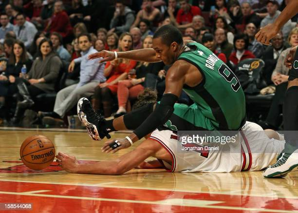 Rajon Rondo of the Boston Celtics lands on top of Joakim Noah of the Chicago Bulls as they battle for a loose ball at the United Center on December...