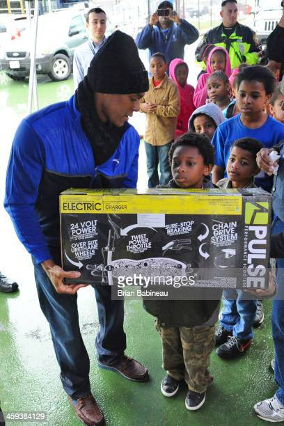 Rajon Rondo of the Boston Celtics spreads holiday cheer and gives Christmas presents to children on December 23 2013 at the Boys and Girls Club in...