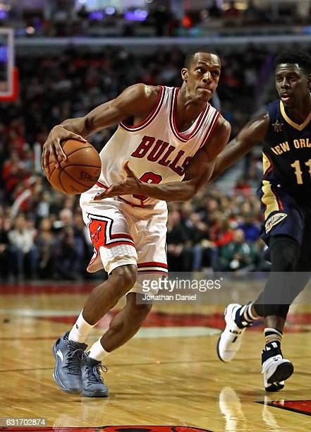 Rajon Rondo of the Chicago Bulls moves past Jrue Holiday of the New Orleans Pelicans at the United Center on January 14 2017 in Chicago Illinois The...