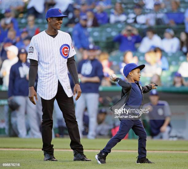 Rajon Rondo of the Chicago Bulls watches as his son Pierre throws a ceremonial first pitch before the Chicago Cubs take on the San Diego Padres at...