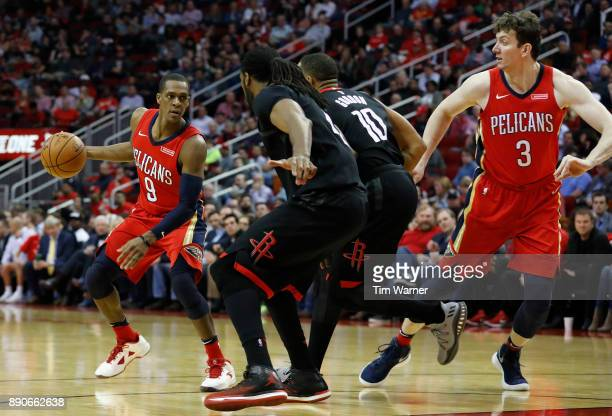 Rajon Rondo of the New Orleans Pelicans dribbles the ball defended by Nene Hilario of the Houston Rockets and Eric Gordon in the second half at...