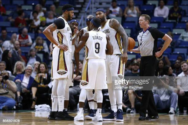 Rajon Rondo of the New Orleans Pelicans talks to DeMarcus Cousins and Anthony Davis during a preseason game against the Chicago Bulls at the Smoothie...