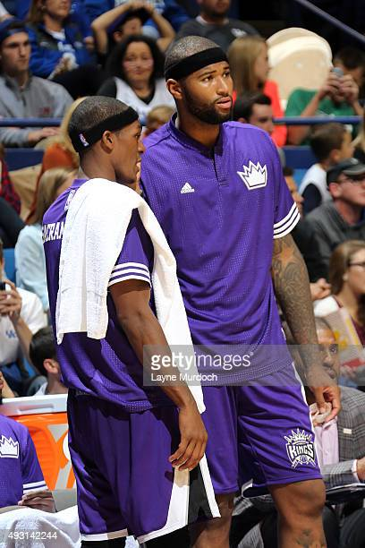 Rajon Rondo of the Sacramento Kings and DeMarcus Cousins of the Sacramento Kings talk on the bench during a preseason game against the New Orleans...