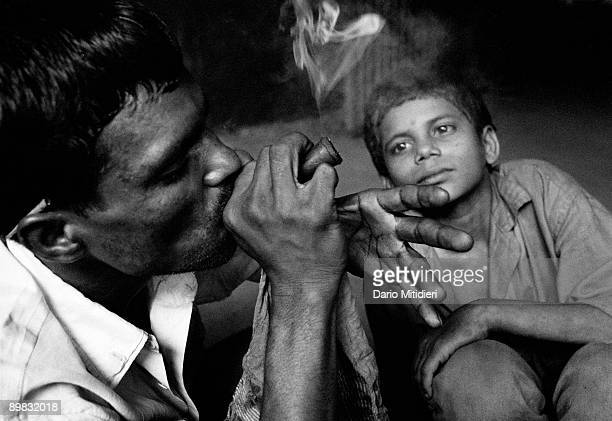 Raju and Muthu smoke a 'Chillum' filled with marijuana near an abandoned railway track at the Victoria Terminus Station
