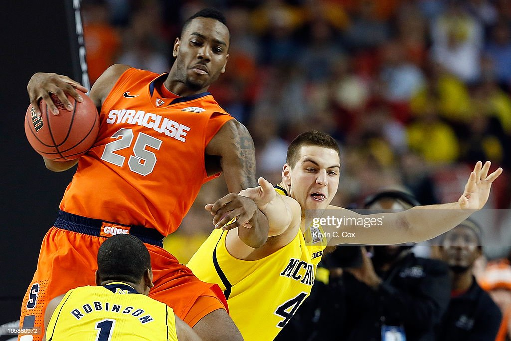 Rakeem Christmas #25 of the Syracuse Orange attempts to control the ball in the first half against Glenn Robinson III #1 and Mitch McGary #4 of the Michigan Wolverines during the 2013 NCAA Men's Final Four Semifinal at the Georgia Dome on April 6, 2013 in Atlanta, Georgia.