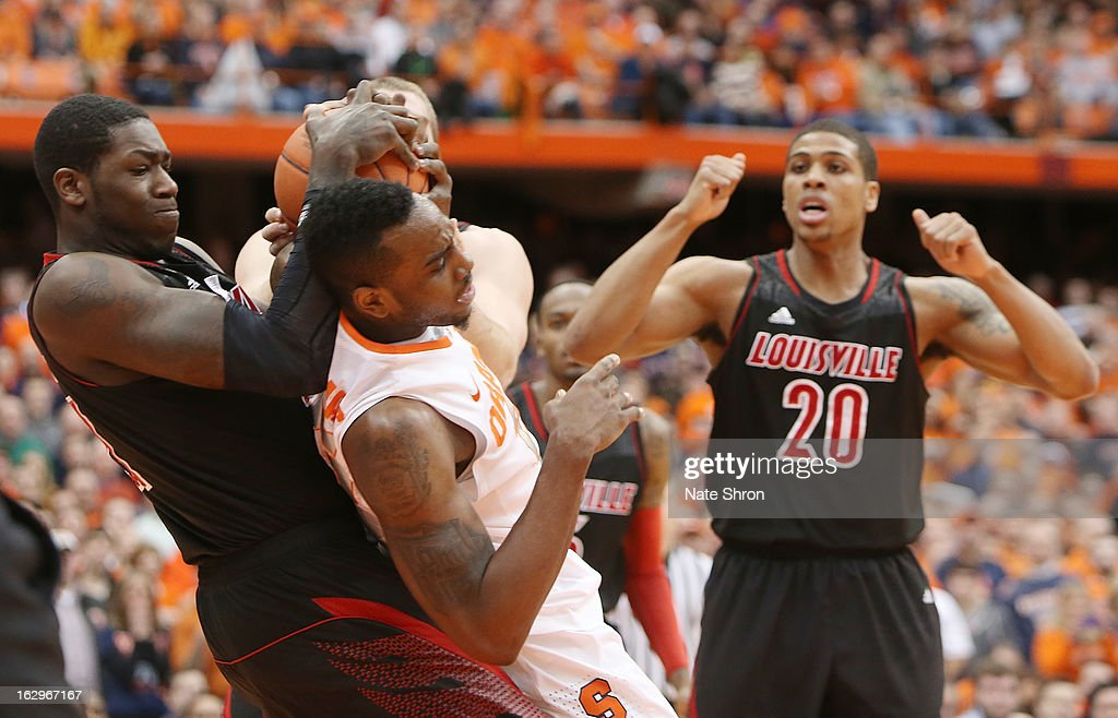 Rakeem Christmas #25 of the Syracuse Orange fights for possession of the ball against Montrezl Harrell #24 and Stephan Van Treese #44 of the Louisville Cardinals as teamate Wayne Blackshear #20 signals jump ball during the game at the Carrier Dome on March 2, 2013 in Syracuse, New York.