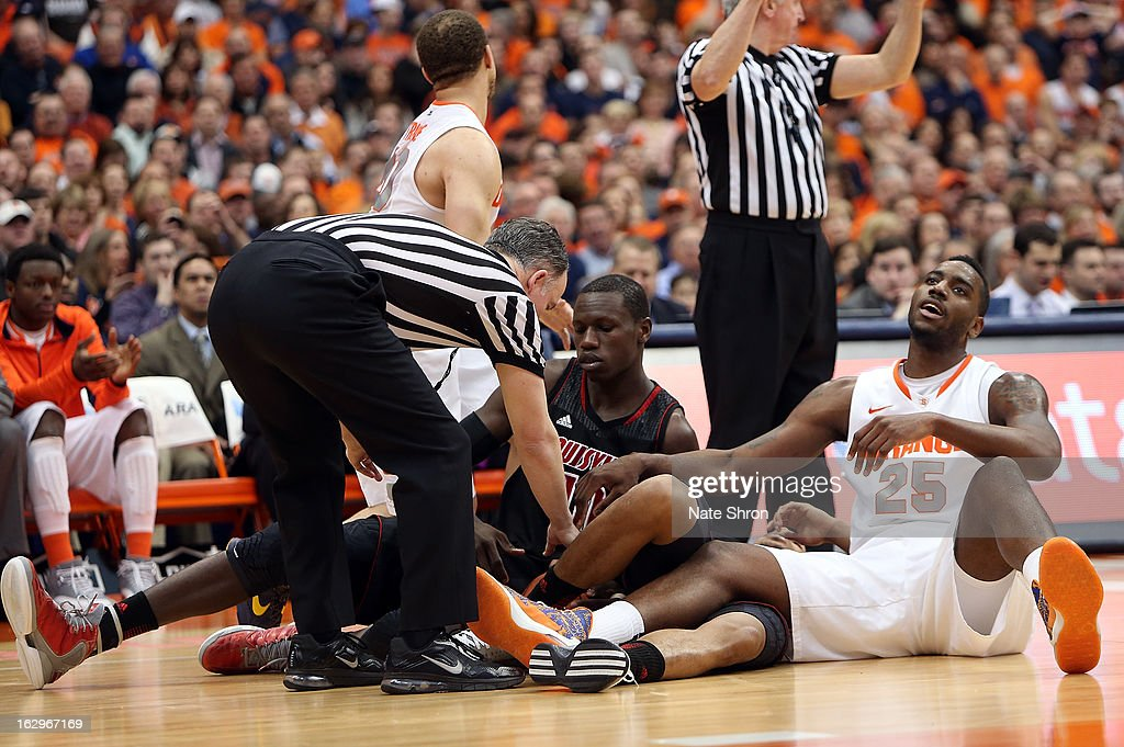 Rakeem Christmas #25 of the Syracuse Orange sits on the floor after fighting for possession against Gorgui Dieng #10 of the Louisville Cardinals during the game at the Carrier Dome on March 2, 2013 in Syracuse, New York.