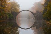Rakotzbrücke (Devil's bridge) in early morning mist, in autumn, Kromlau, Germany