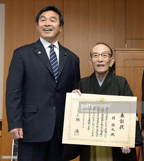 'Rakugo' or Japanese sitdown comedy performer Utamaru Katsura receives an award from Hiroshi Hase minister of education culture sports science and...
