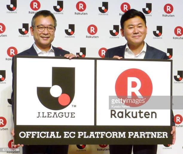 Rakuten Chief Executive Officer Hiroshi Mikitani holds a sign with JLeague Chairman Mitsuru Murai in Tokyo on April 24 as the pair announce a tieup...