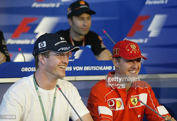 Ralf Schumacher of Germany and Williams enjoys a joke with his brother Michael of Ferrari as Heinz Harald Frentzen looks on during an FIA Press...