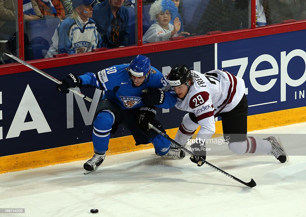 Ralfs Freibergs (R) of Latvia and Juhamatti Aaltonen (L) of Finland battle for the puck during the IIHF World Championship group H match between Latvia and Finland at Hartwall Areena on May 14, 2013 in Helsinki, Finland.