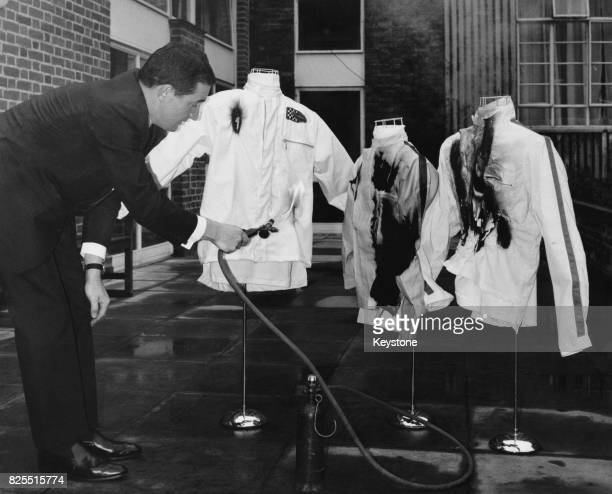 Rally driver Paddy Hopkirk demonstrates a new fireresistant cloth by DuPont at the Kensington Close Hotel in London 27th November 1967