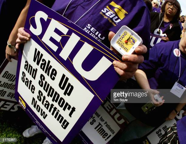 A rally participant displays her demonstration sign and small alarm clock during a nurse's rally October 19 2001 in Chicago The rally and the...