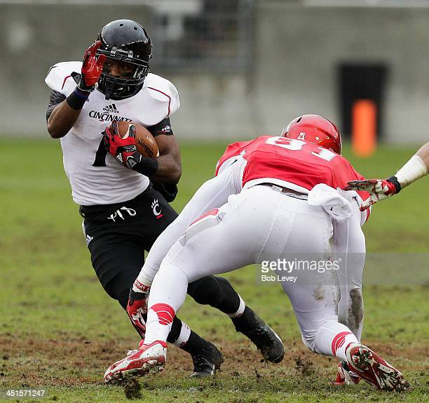 Ralph Abernathy of the Cincinnati Bearcats avoids a tackle by Tyus Bowser at BBVA Compass Stadium on November 23 2013 in Houston Texas