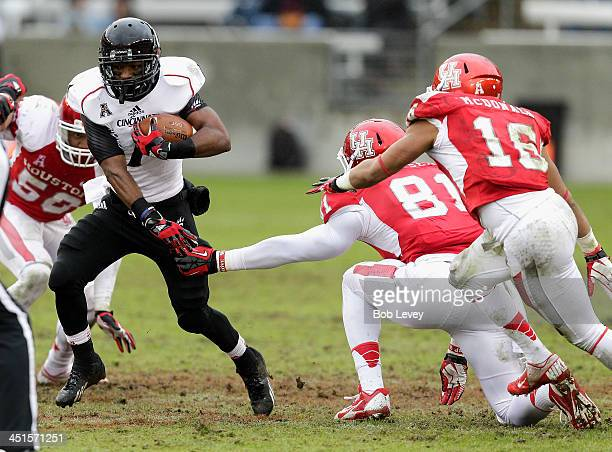 Ralph Abernathy of the Cincinnati Bearcats avoids a tackle by Tyus Bowser of the Houston Cougars and Adrian McDonald at BBVA Compass Stadium on...