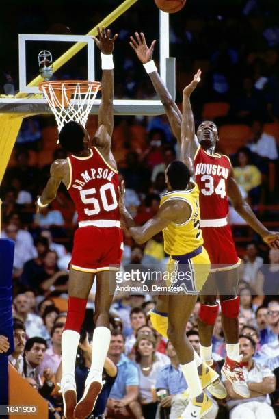 Ralph Sampson and Hakeem Olajuwon of the Houston Rockets battle for a rebound during the 1984 NBA game against Magic Johnson of the Los Angeles...