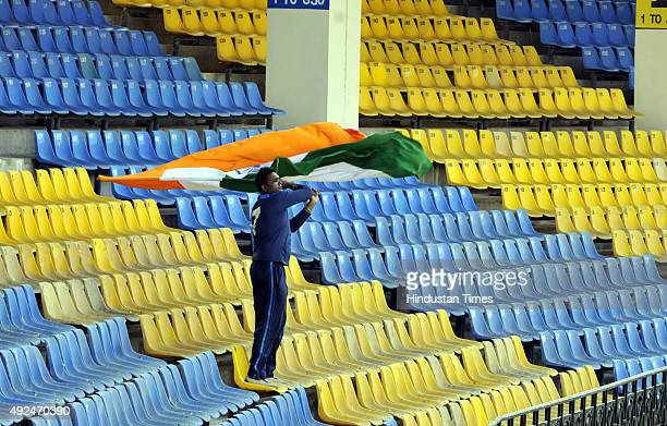Ram Babu a supporter of team India who gets sponsorship from team captain Mahendra Singh Dhoni waves the Indian tricolour at Holkar Stadium during...