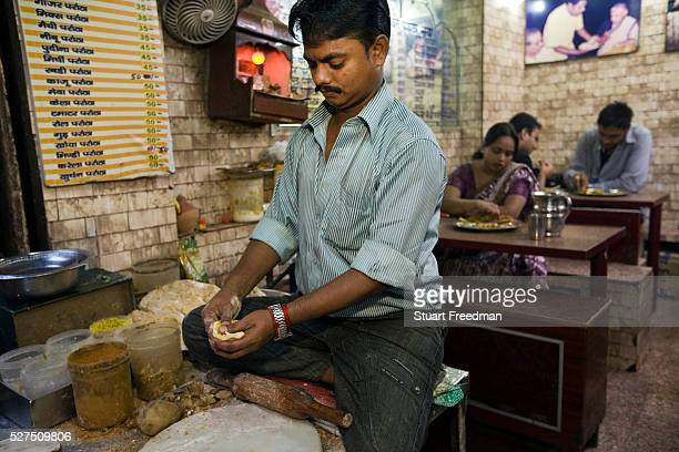 Ram Billas making paratha at Parawthe Wala restaurant in Old Delhi India The parantha is an Indian fried bread folded and filled with fillings and...