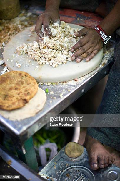 Ram Billas's foot resting on a tin whilst making paratha at Parawthe Wala restaurant in Old Delhi India The parantha is an Indian fried bread folded...