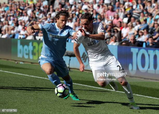 Ramadan Sobhi of Stoke City challenges Gylfi Sigurdsson of Swansea City during the Premier League match between Swansea City and Stoke City at The...
