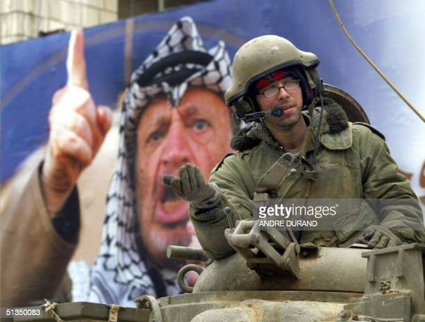 An Israeli soldier gestures from his tank in front of a banner of Palestinian leader Yasser Arafat in the West Bank city of Ramallah 31 March 2002...