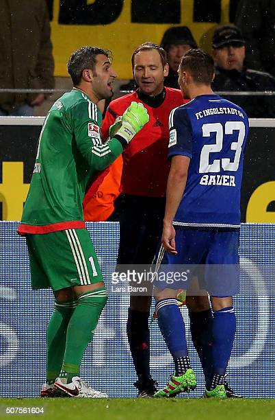 Ramazan Oezcan of Ingolstadt and Robert Bauer of Ingolstadt discus with assistant referee Arno Blos during the Bundesliga match between Borussia...