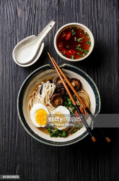 Ramen noodles with egg, enoki and shiitake mushrooms with broth on dark wooden background