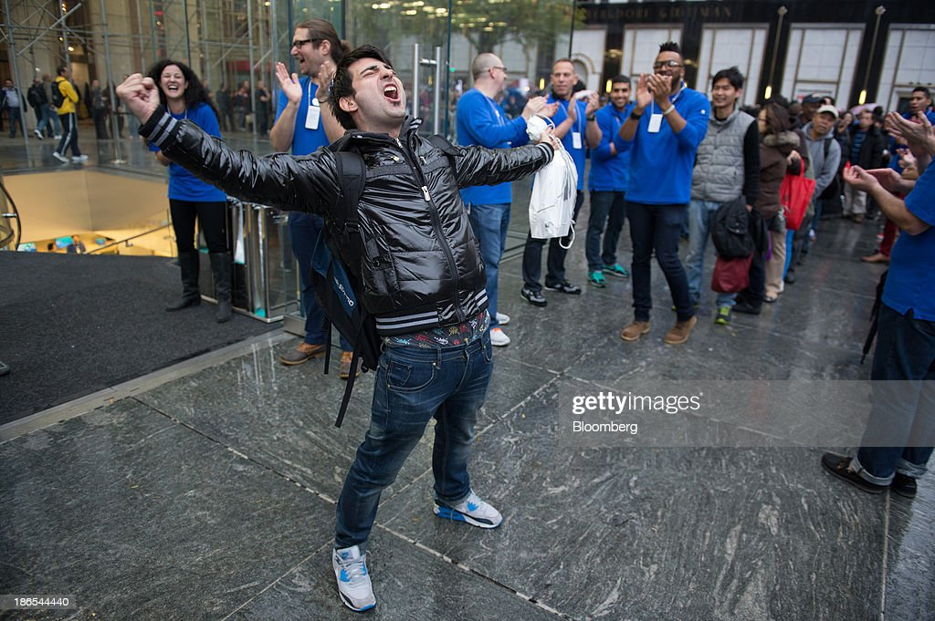 Rami Shamis celebrates after being the first to buy the new Apple Inc. iPad Air at the 5th Avenue Apple store in New York, U.S., on Friday, Nov. 1, 2013. Apple Inc.'s forecast for the slowest holiday sales growth in a half decade reflects how iPhones and iPads arent providing the growth surges they once did as competition accelerates in the saturated mobile market. Photographer: Craig Warga/Bloomberg via Getty Images