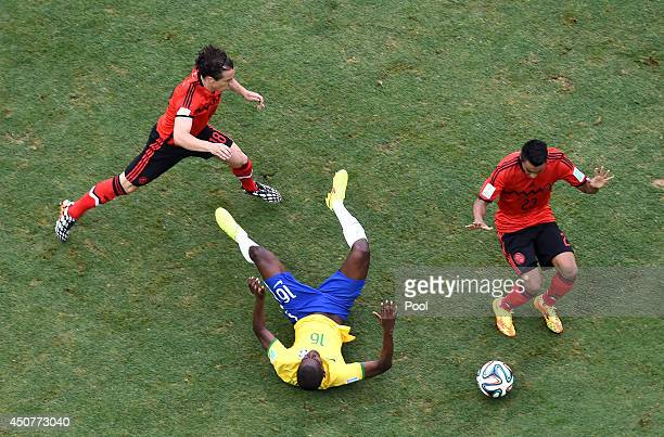 Ramires of Brazil falls after a challenge by Andres Guardado and Jose Juan Vazquez of Mexico during the 2014 FIFA World Cup Brazil Group A match...