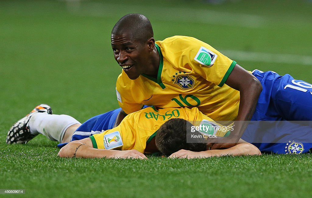 Ramires of Brazil pulls Oscar to the ground in celebration after his goal in the second half during the 2014 FIFA World Cup Brazil Group A match between Brazil and Croatia at Arena de Sao Paulo on June 12, 2014 in Sao Paulo, Brazil.
